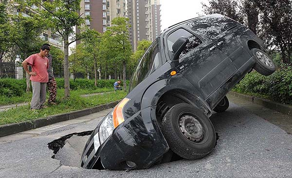 SUV vehicle sinks into the road after heavy rain in Hangzhou, Zhejiang, China - 19 Jun 2012